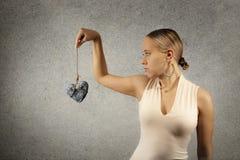 Belle jeune femme en tissus occasionnels tenant le coeur en pierre dans l'esclavage de jute sur le fond gris de mur de texture Images stock