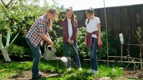 Belle jeune femme enseignant ses enfants prenant soin de jardin images stock