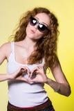 Belle jeune femme espiègle avec des lunettes de soleil Photo libre de droits