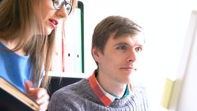 Belle jeune femme et homme travaillant du siège social clips vidéos