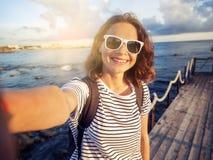 Belle jeune femme faisant le selfie sur le backgroun de mer et de ville Photographie stock libre de droits