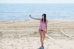 Belle jeune femme faisant le selfie sur la plage Photo stock