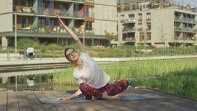 Belle jeune femme faisant le yoga dehors près de la maison banque de vidéos