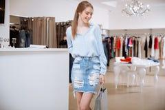 Belle jeune femme gaie faisant des achats dans le magasin d'habillement Image stock