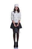 Belle jeune femme gaie utilisant le chandail, la jupe, le chapeau et le sac à dos tricotés D'isolement sur le fond blanc images stock