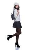 Belle jeune femme gaie utilisant le chandail, la jupe, le chapeau et le sac à dos tricotés D'isolement sur le fond blanc photos stock