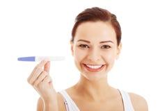 Belle jeune femme heureuse avec l'essai de grossesse. Photos stock