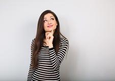 Belle jeune femme heureuse avec le doigt sous le visage imaginant et regardant dans la chemise occasionnelle et les longs cheveux photographie stock