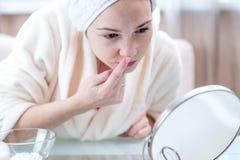 Belle jeune femme heureuse avec une serviette sur la tête regardant sa peau dans un miroir Hygiène et entretenir opportuns la pea photographie stock