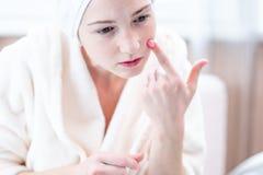 Belle jeune femme heureuse avec une serviette sur la tête regardant sa peau dans un miroir Hygiène et entretenir opportuns la pea image stock