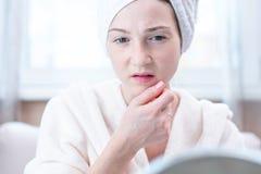 Belle jeune femme heureuse avec une serviette sur sa tête regardant sa peau dans un miroir Hygiène et entretenir la peau photographie stock