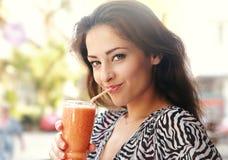 Belle jeune femme heureuse buvant l'outd sain de jus de smoothie Photographie stock