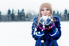 Belle jeune femme heureuse espiègle sexy mignonne dans un manteau bleu dans le chapeau jouant avec la neige en parc Photographie stock libre de droits