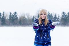Belle jeune femme heureuse espiègle sexy mignonne dans un manteau bleu dans le chapeau jouant avec la neige en parc Image libre de droits