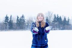 Belle jeune femme heureuse espiègle sexy mignonne dans un manteau bleu dans le chapeau jouant avec la neige en parc Images libres de droits