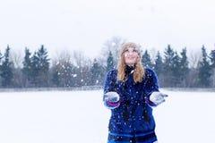 Belle jeune femme heureuse espiègle sexy mignonne dans un manteau bleu dans le chapeau jouant avec la neige en parc Photographie stock