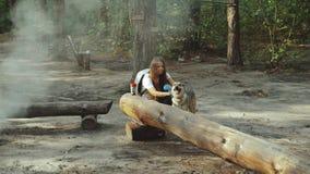 Belle jeune femme heureuse frottant son chien affectueux dans la forêt clips vidéos