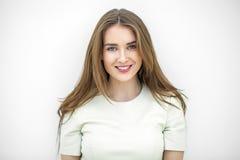 Belle jeune femme heureuse posant contre un mur blanc photographie stock libre de droits