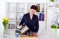 Belle jeune femme heureuse préparant le thé à la maison Photos libres de droits