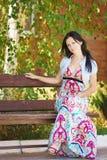 Belle jeune femme heureuse s'asseyant sur un banc de parc Images stock