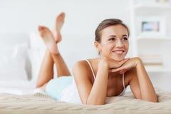 Belle jeune femme heureuse se trouvant sur le lit à la maison Photos libres de droits