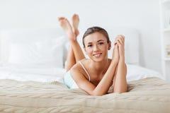 Belle jeune femme heureuse se trouvant sur le lit à la maison Photographie stock