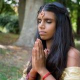 Belle jeune femme indienne priant en parc Image libre de droits