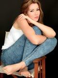 Belle jeune femme insouciante réfléchie heureuse s'asseyant dans une chaise Image libre de droits