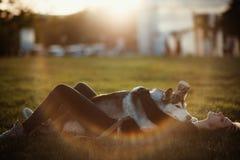 Belle jeune femme jouant avec le chien enroué drôle dehors en parc au coucher du soleil ou au lever de soleil Photographie stock libre de droits