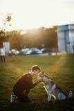 Belle jeune femme jouant avec le chien enroué drôle dehors en parc au coucher du soleil ou au lever de soleil Photos libres de droits