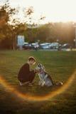 Belle jeune femme jouant avec le chien enroué drôle dehors en parc au coucher du soleil ou au lever de soleil Image libre de droits
