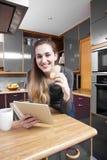 Belle jeune femme joyeuse tenant un comprimé numérique dans la cuisine Images libres de droits