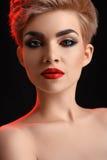 Belle jeune femme labiée rouge blonde posant en rouge artistique l Photos stock