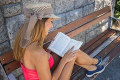 Belle jeune femme lisant un livre sur un banc photos libres de droits