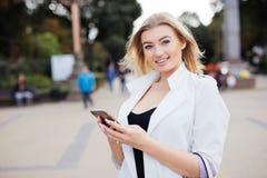 Belle jeune femme magnifique avec la transmission de messages de cheveux blonds sur le Smart-téléphone au fond de rue de ville photo libre de droits