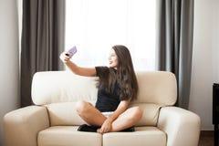 Belle jeune femme magnifique prenant un selfie dans la chambre Photographie stock libre de droits