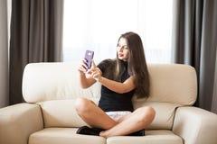Belle jeune femme magnifique prenant un selfie dans la chambre Photo stock