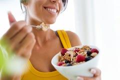 Belle jeune femme mangeant des céréales et des fruits à la maison photographie stock libre de droits
