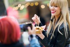 Belle jeune femme mangeant des pommes de terre tandis que son ami prenant une photo dans la rue Photos stock