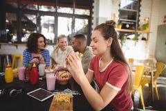 Belle jeune femme mangeant l'hamburger tout en se reposant au café Image stock