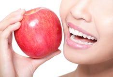 Jeune femme mangeant la pomme rouge avec des dents de santé Photo libre de droits