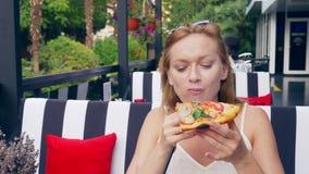 Belle jeune femme mangeant une tranche de pizza en café plan rapproché, 4k, au ralenti banque de vidéos