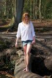 Belle jeune femme marchant à travers un rondin au-dessus de courant photo libre de droits