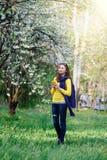 Belle jeune femme marchant dans le jardin luxuriant de ressort Photographie stock