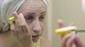 Belle jeune femme mettant le mascara devant le miroir dans la salle de bains banque de vidéos