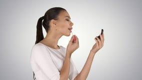 Belle jeune femme mettant sur le rouge à lèvres sur le fond de gradient images stock