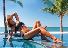 Belle jeune femme mince dans le bain de soleil de chapeau de paille et de lunettes de soleil Photo stock