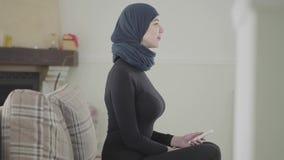 Belle jeune femme musulmane à l'aide de l'extérieur pour tourner à la TV portant le foulard traditionnel sur le fond de confortab banque de vidéos