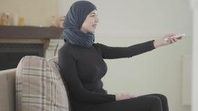 Belle jeune femme musulmane sûre réussie à l'aide de l'extérieur pour tourner à la TV portant le foulard traditionnel dessus banque de vidéos