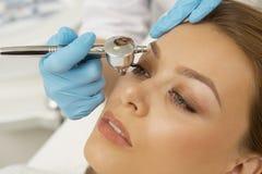 Belle jeune femme obtenant des injections de beauté dans son visage photos libres de droits